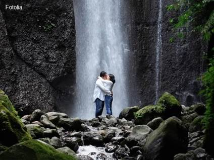 Couple kissing in front of a waterfall
