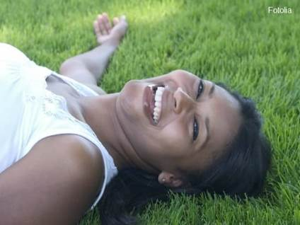Woman lying in grass, laughing