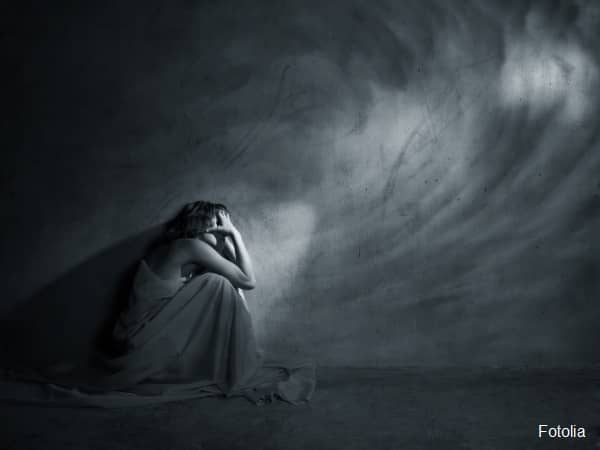 Woman crouching in dark room with head in hands