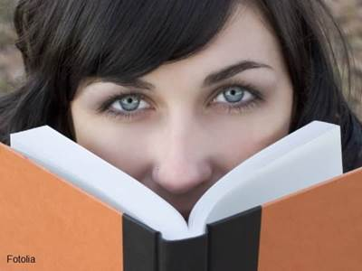 Woman peeking over the top of a book