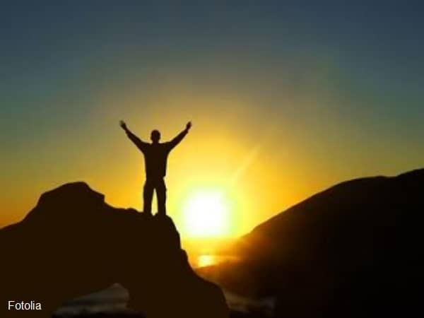 Silhouette of man with arms raised in front of rising sun