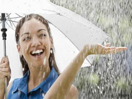 Smiling woman under umbrella in heavy rain